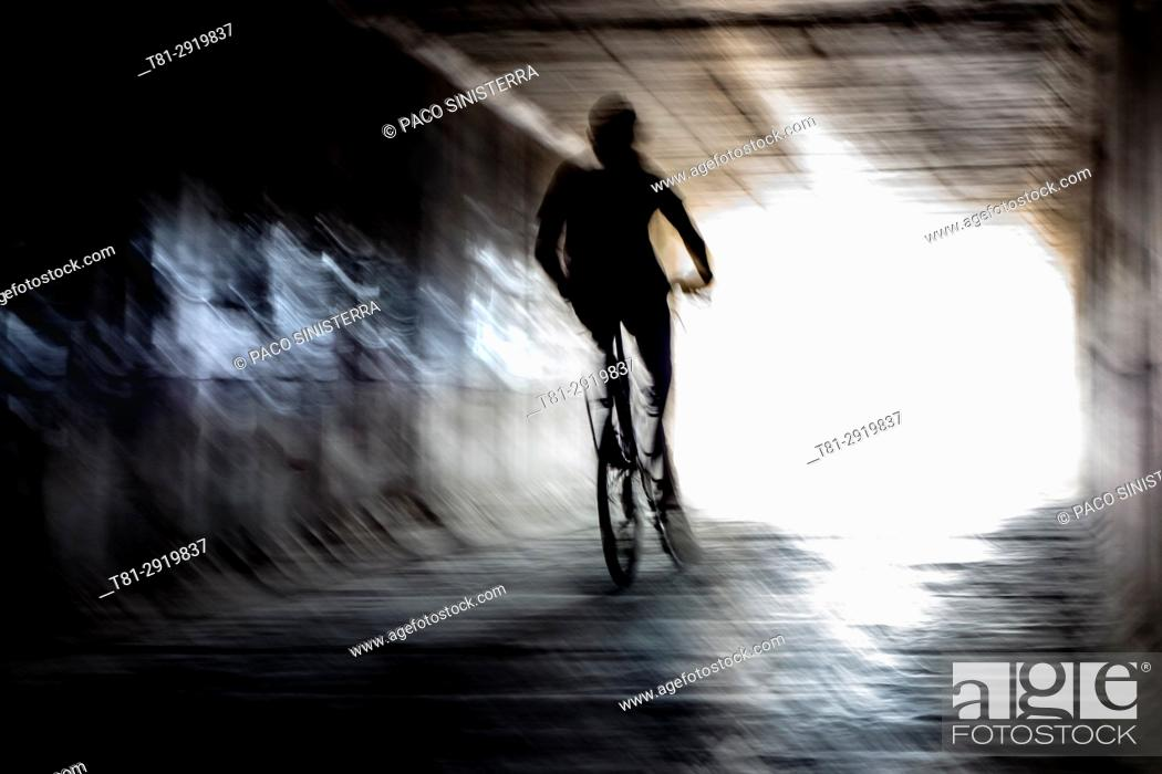 Stock Photo: Boy on a bike crossing a tunnel, Alboraya, Spain.