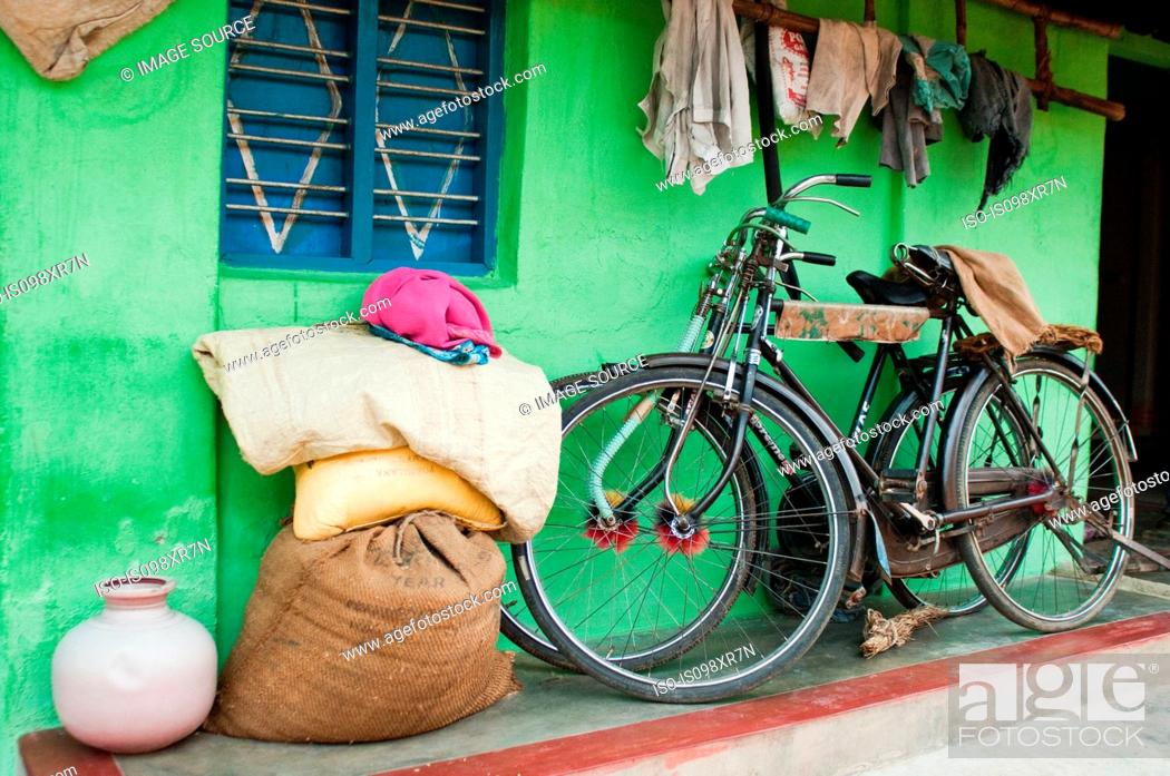 Stock Photo: Bicycles and hessian sacks and rags outside village house near Mysore, Karnataka.