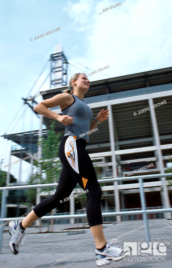 Stock Photo: A young athletic woman, 15-20 20-25 25-30 years old, blond, sporty, running, jogging.