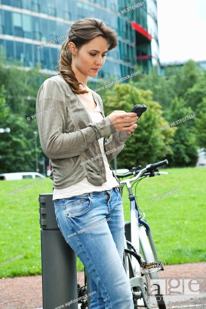 Stock Photo: Germany, Berlin, Woman using cell phone besides bicycle.