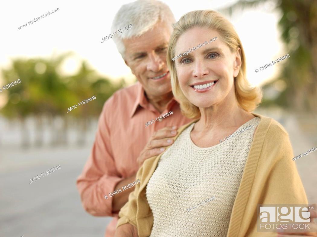 Stock Photo: Senior couple palm trees in background.