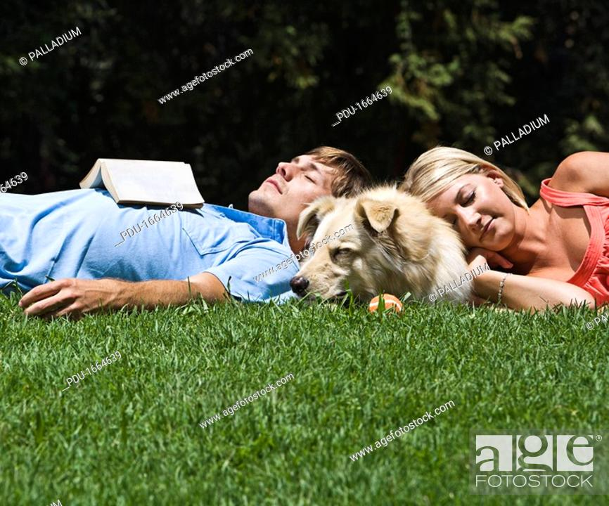 Stock Photo: Couple lying on grass with dog.