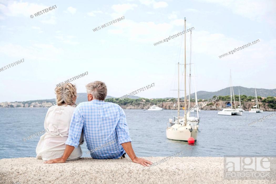 Stock Photo: Spain, Senior couple sitting at harbour.
