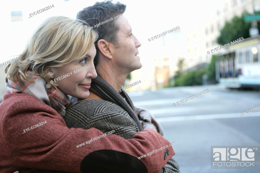 Stock Photo: Mature couple embracing in the street.