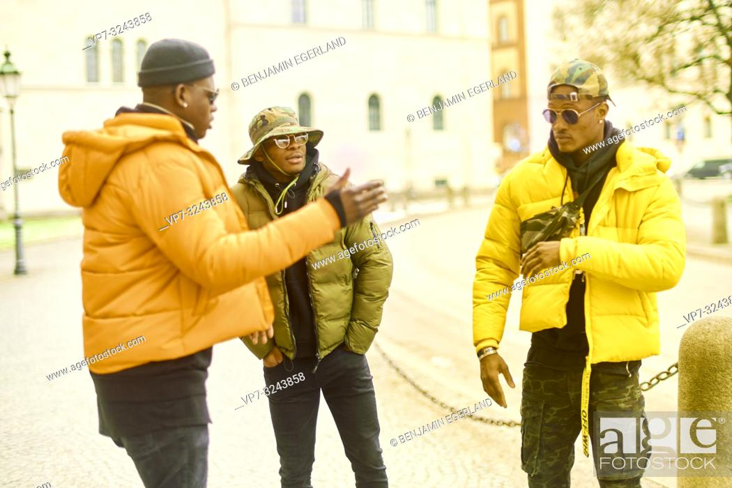 Stock Photo: three stylish male friends hanging out at street, urban streetwear, youth culture, Munich, Germany.