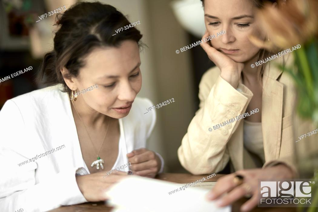 Stock Photo: two stylish friends reading menu card in restaurant.