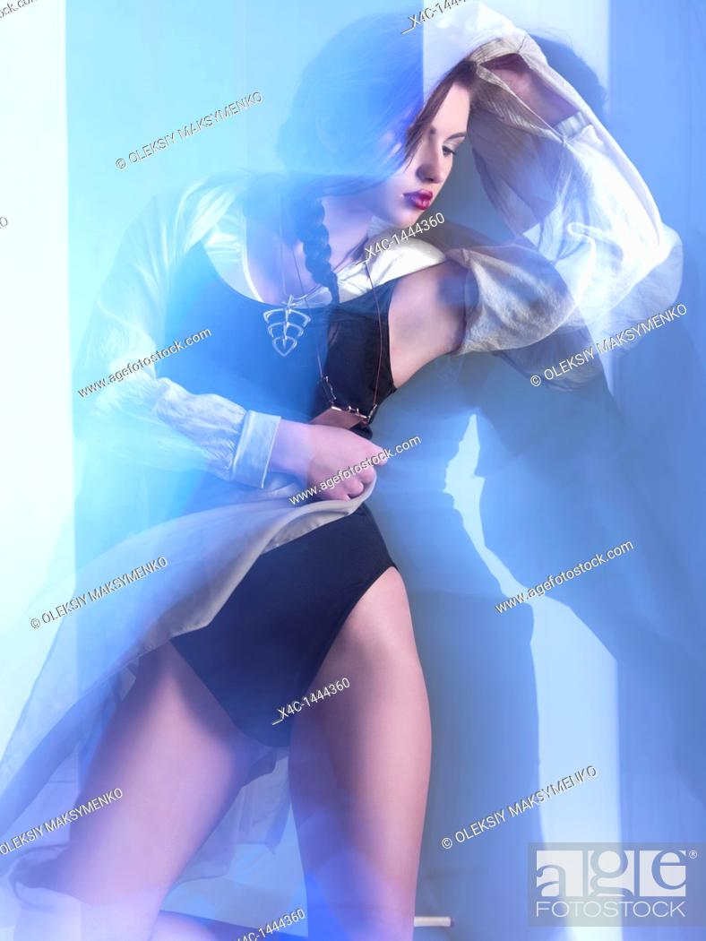 Stock Photo: Futuristic dynamic high fashion photo of a young woman in trendy clothes posing in shiny neon light settings  The photo was not digitally manipulated.