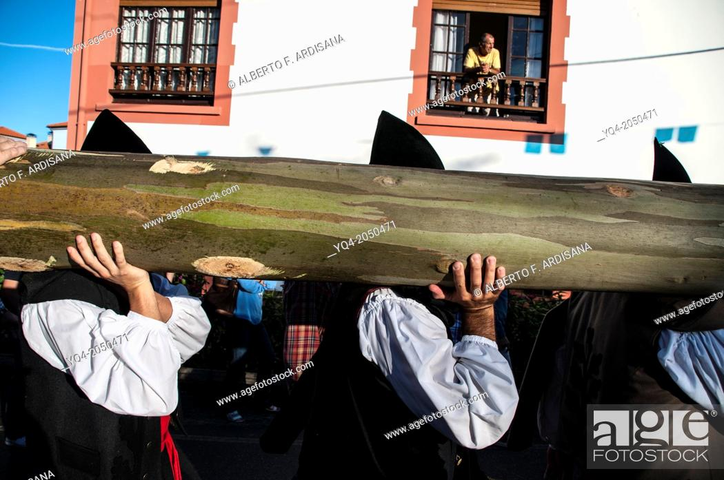 Stock Photo: Men dressed in traditional costume Llanes, shoulder carry eucalyptus trunk. festival of Nueva de Llanes. Asturias Spain.