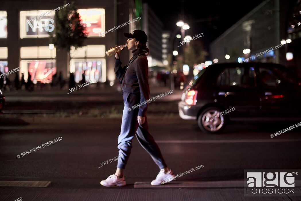 Imagen: woman drinking from bottle on street in Berlin, Germany.
