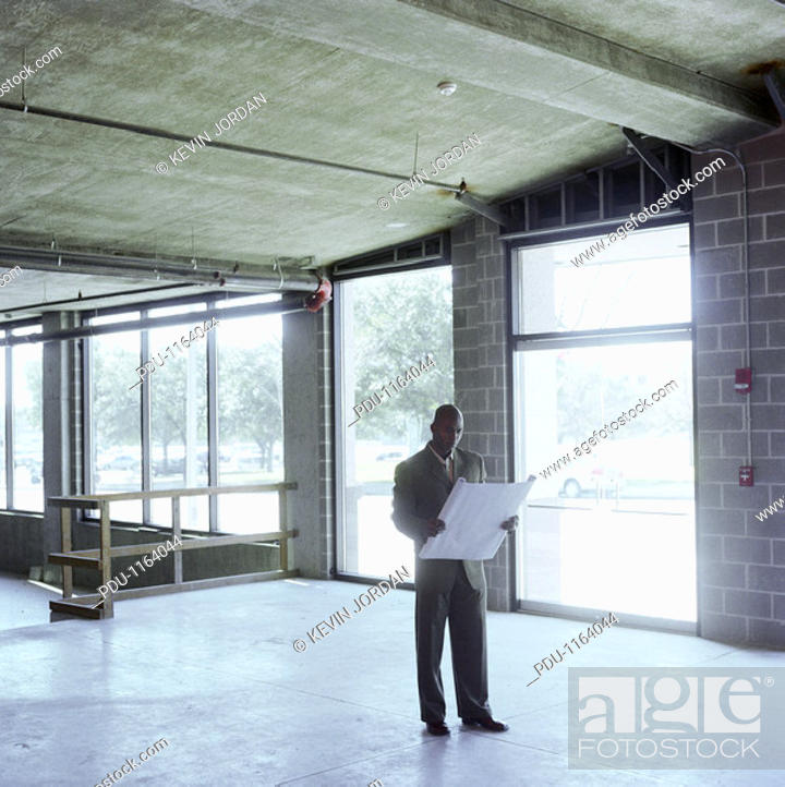 Stock Photo: Man looking at blue print, standing in empty retail space.