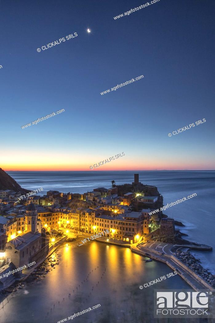 Stock Photo: A moonlit night leaving the scene to the first lights of the sunrise over the pictoresque village of Vernazza and its harbor.