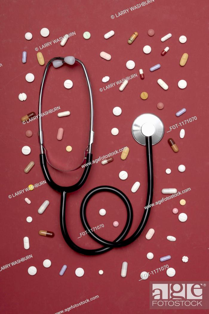 Stock Photo: A stethoscope lying amongst various pills.