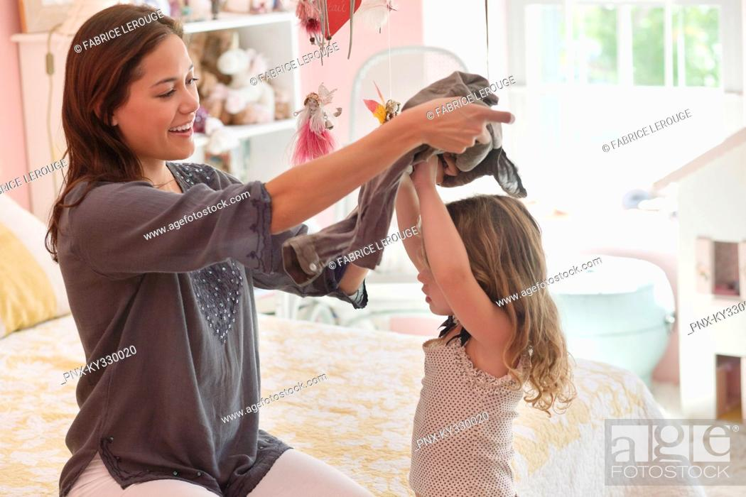 Stock Photo: Happy woman dressing her daughter at home.