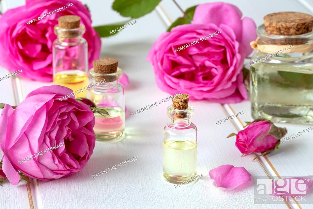 Stock Photo: A bottle of essential oil with fresh roses.