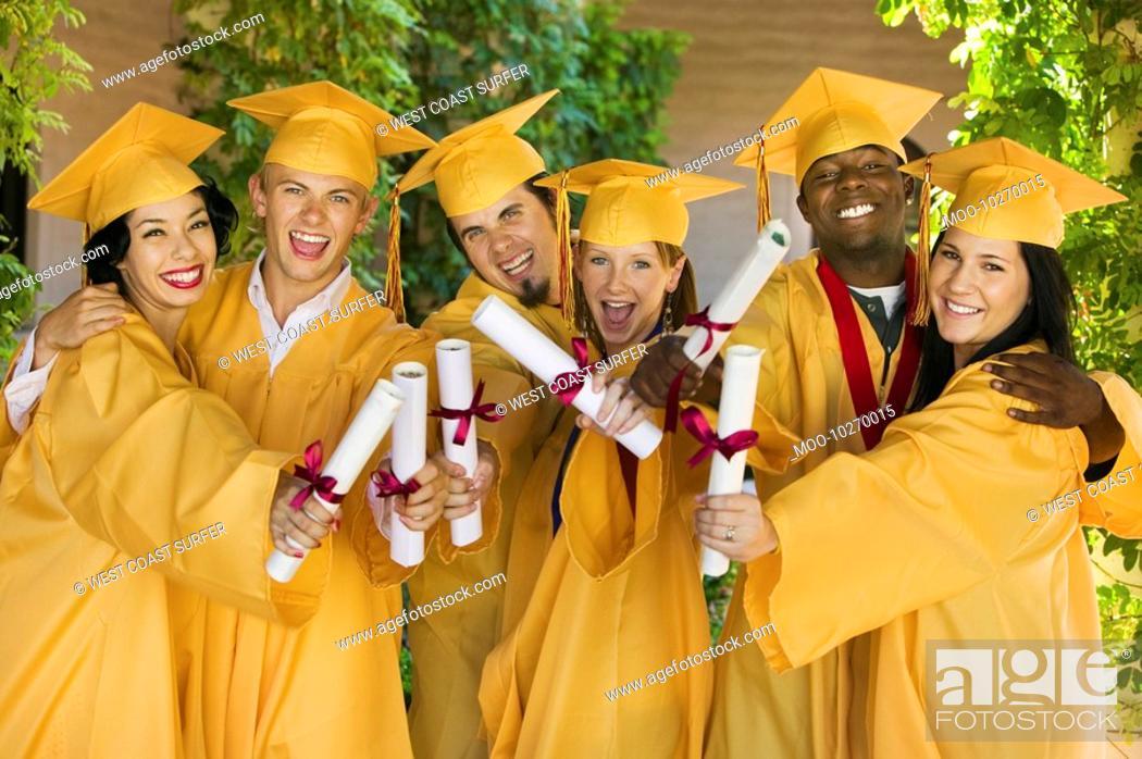 Stock Photo: Group of graduates holding diplomas outside portrait.