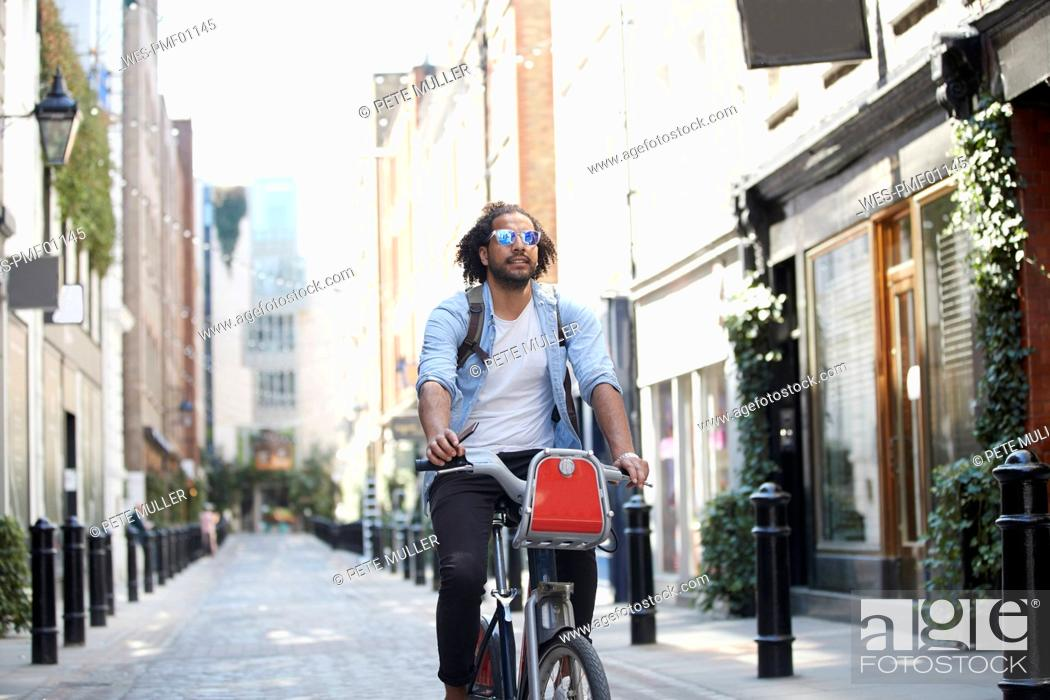 Stock Photo: Portrait of young man riding on rental bike in the city, London, UK.