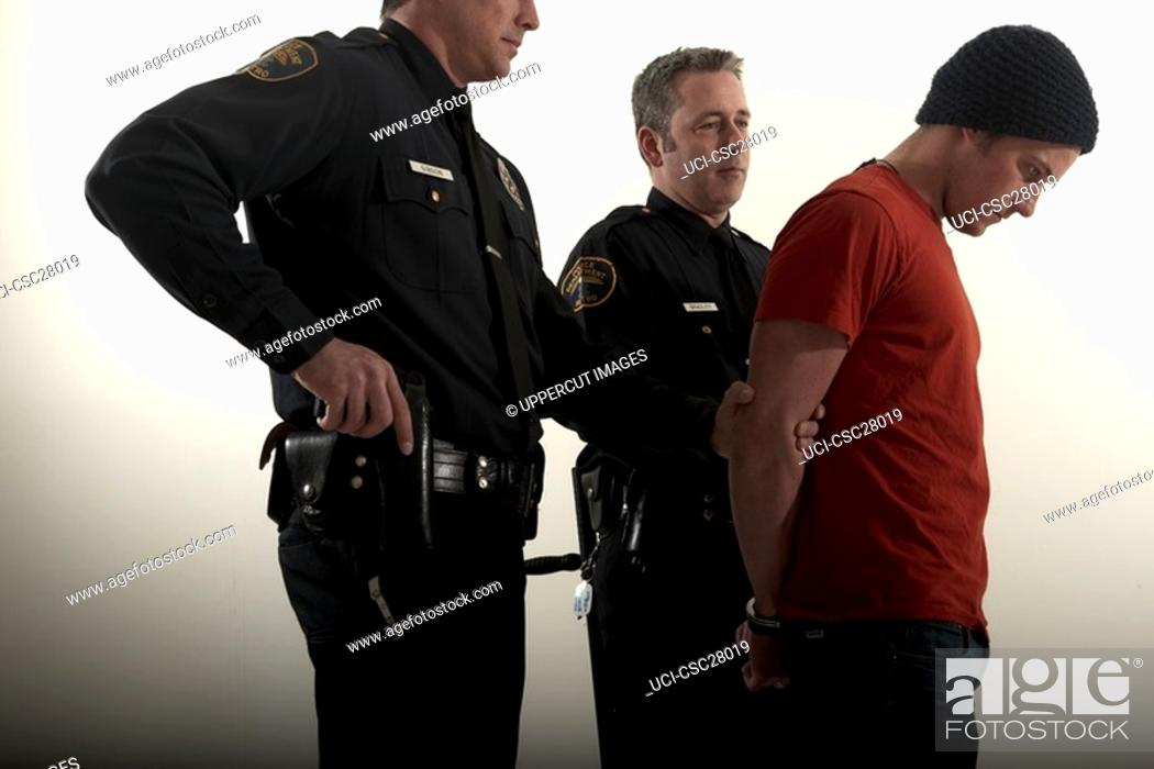 Stock Photo: Male police officers arresting a young man.