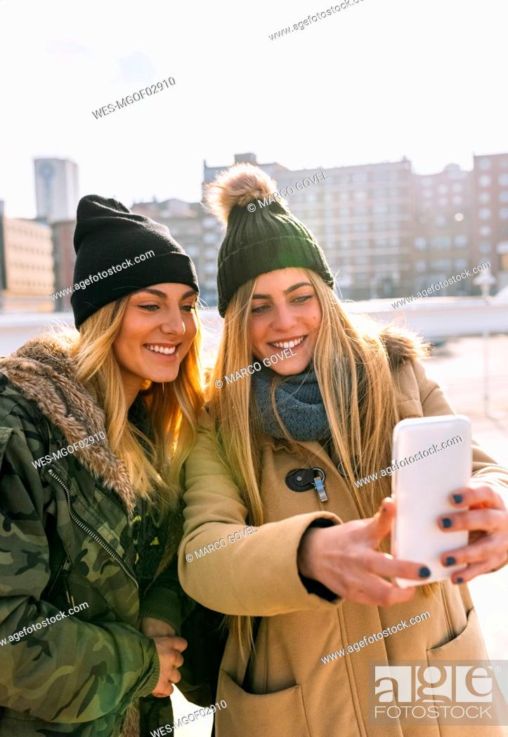 Stock Photo: Two friends taking selfie with smartphone.