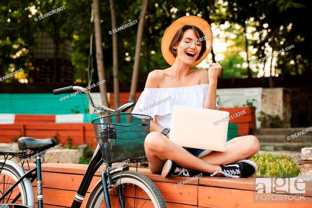 Stock Photo: Excited young girl dressed in summer clothes using laptop computer while sitting at the park.