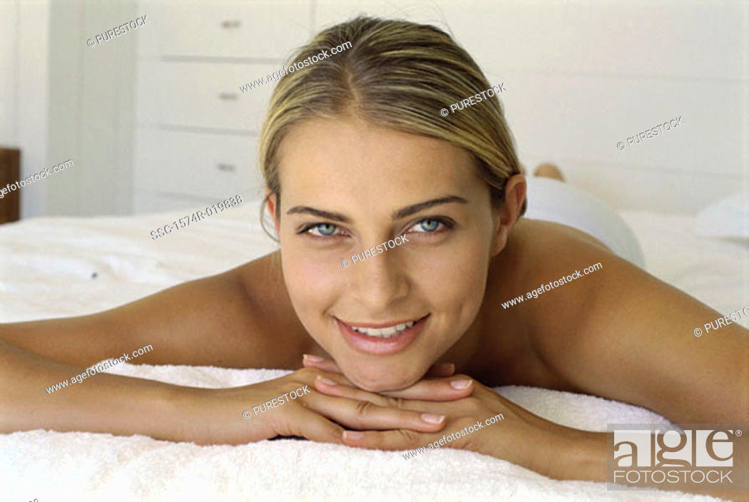 Stock Photo: Portrait of a young woman lying on the bed.