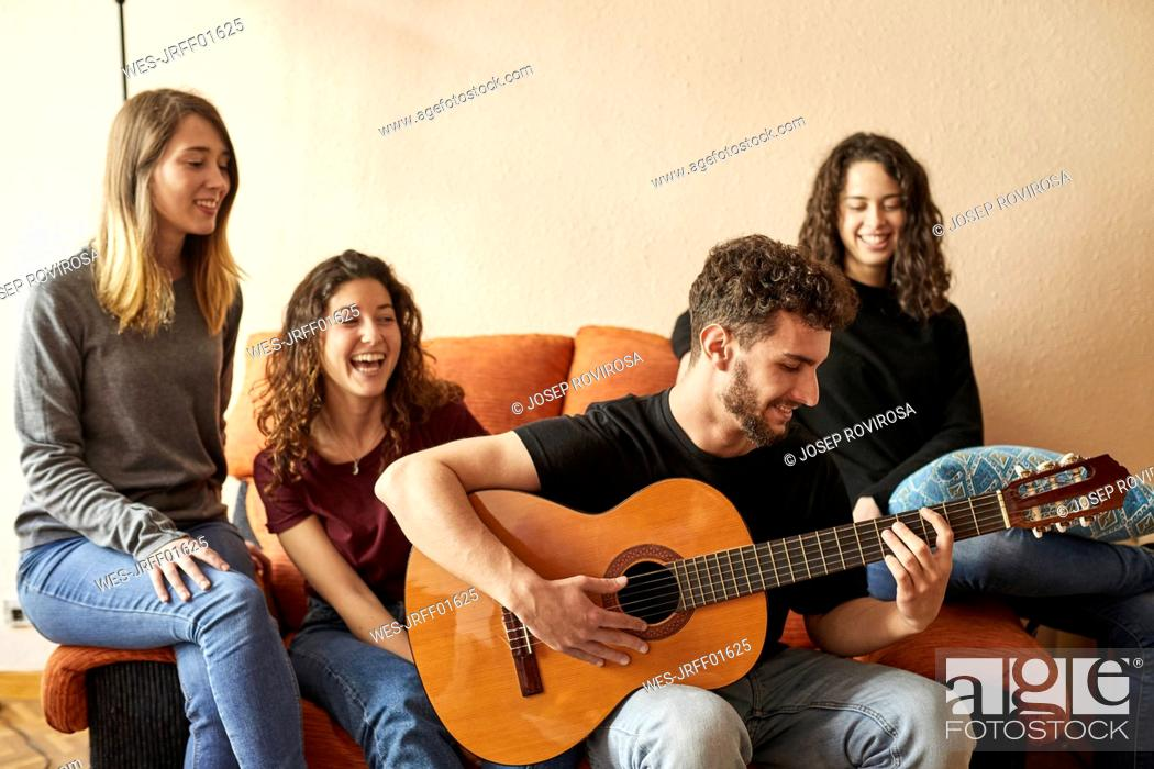 Imagen: Happy freinds listening to man playing guitar on couch.