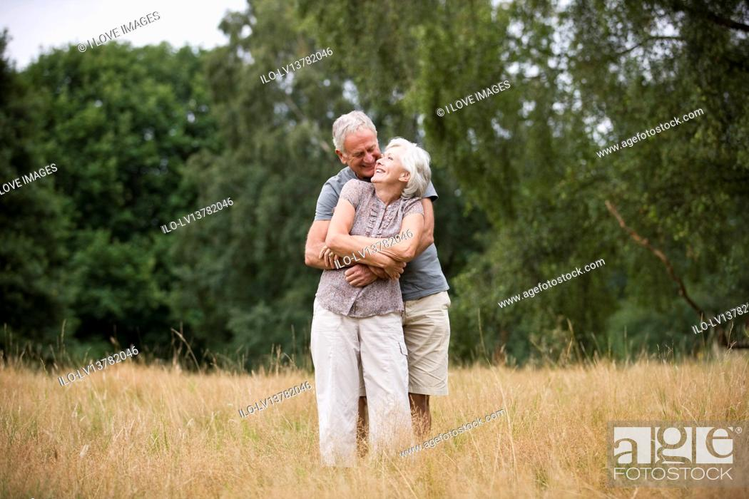 Stock Photo: A senior couple standing in a field, embracing.