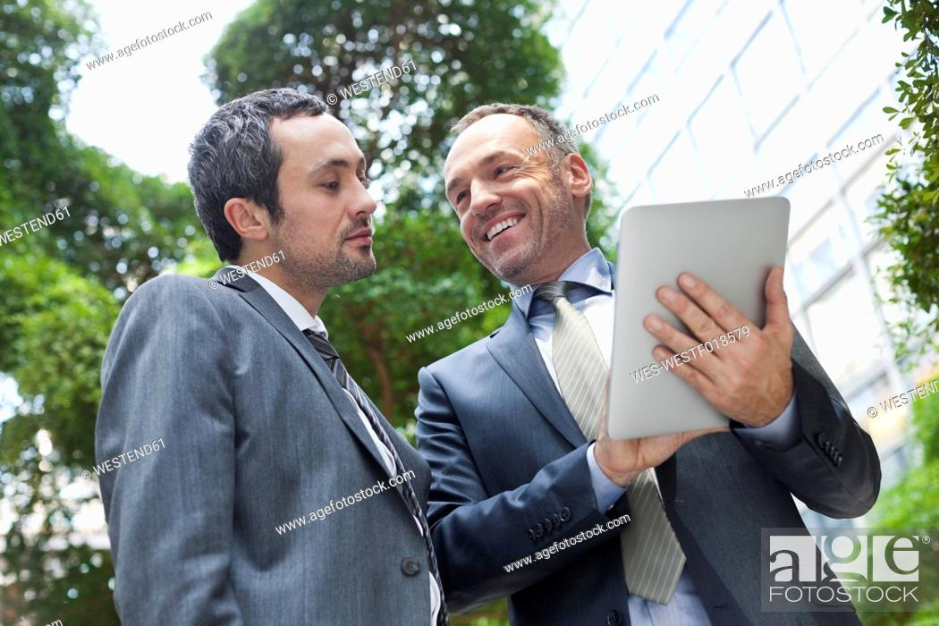 Stock Photo: Germany, Leipzig, Business people using digital tablet.