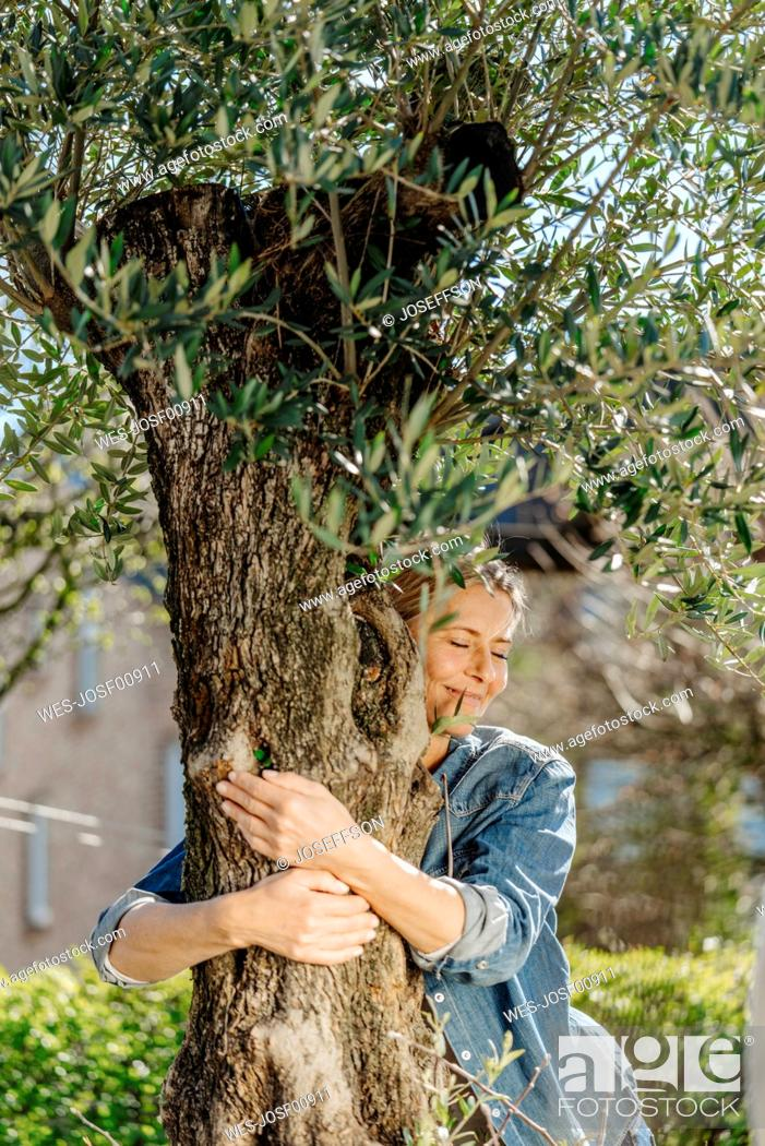 Stock Photo: Woman in garden hugging a tree.