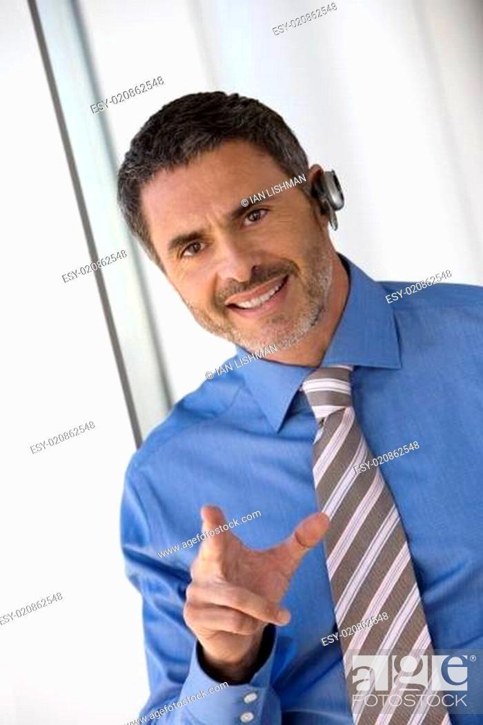 Stock Photo: Businessman wearing mobile phone hands-free device, making hand sign, smiling, portrait (tilt).