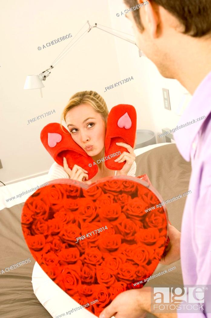 Stock Photo: Young man giving a pair of slippers to a young woman.