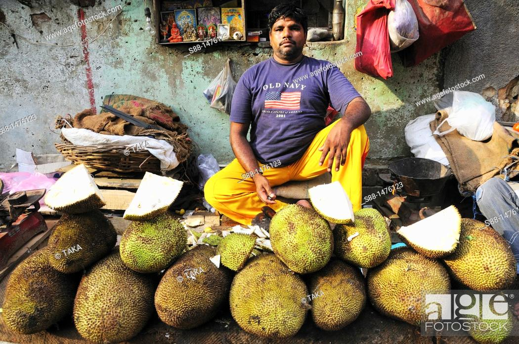 Stock Photo: Man at the market selling Jack fruits, New Delhi, India.