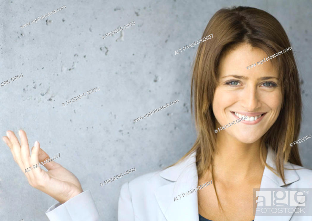 Stock Photo: Young businesswoman smiling and holding up hand, portrait.