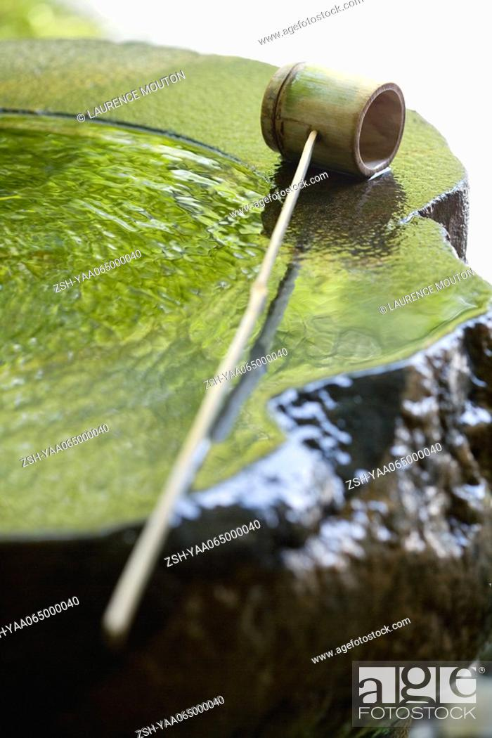 Stock Photo: Bamboo ladle on water fountain, close-up.
