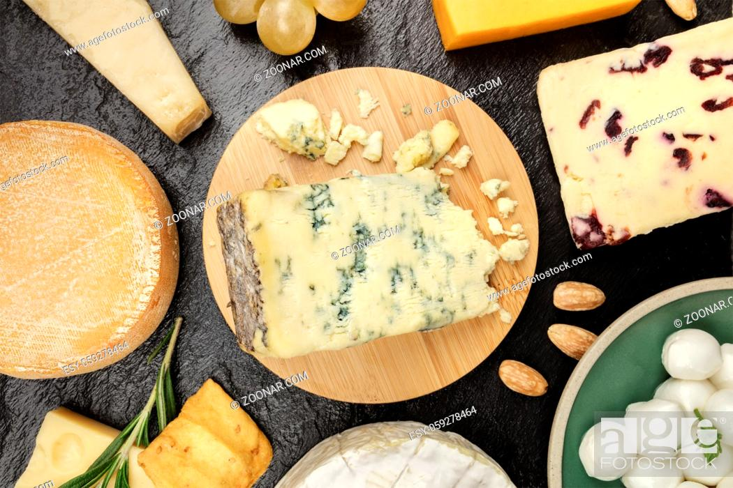 Stock Photo: An assortment of various types of cheese, shot from above on a black background texture.