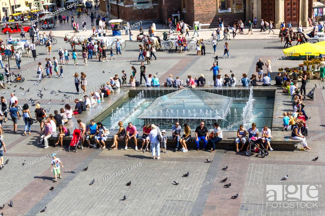 Stock Photo: Tourists walking and resting at the fountain in the Old Market Square, view from above, Krakow, Poland.