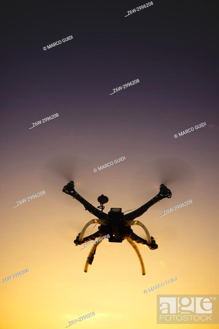 Stock Photo: Photographic representation of the flight of a quadrocopter at sunset.