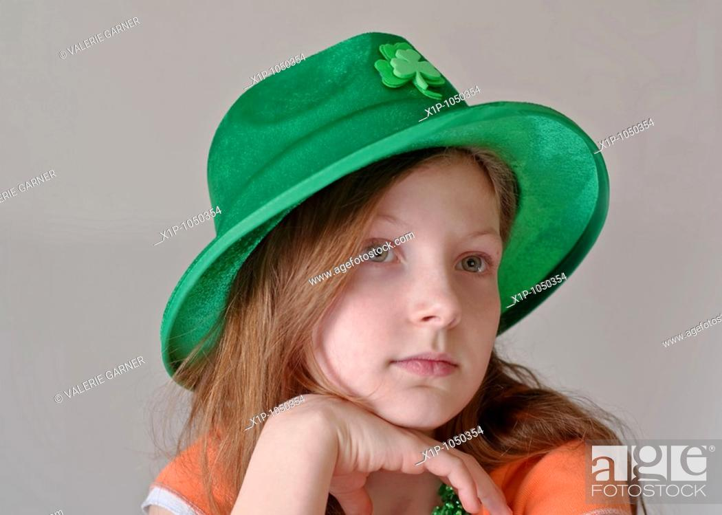 Stock Photo: This beautiful green eyed, 9 year old Caucasian girl is wearing a green St Patrick's Day hat in a closeup on a light background Her facial expression is a more.