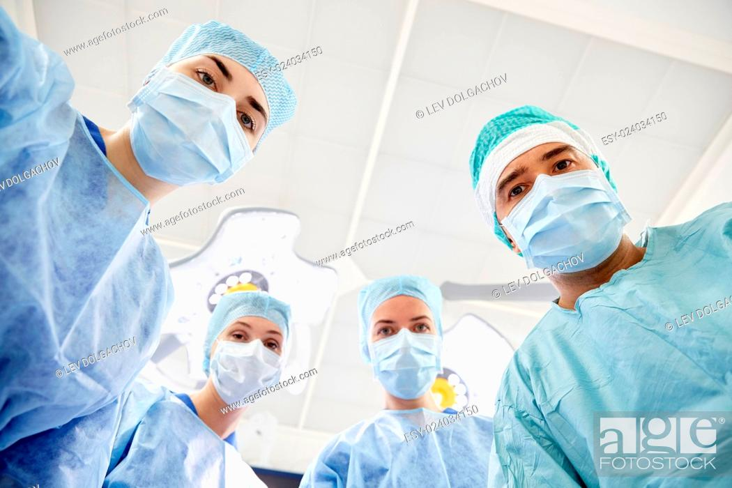 Stock Photo: surgery, medicine and people concept - group of surgeons in operating room at hospital looking into camera.