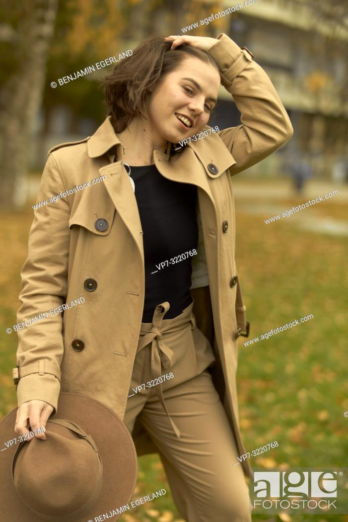 Stock Photo: young playful woman walking outdoors in park during autumn season, ruffling hair, wearing coat, prankish, coquettish, smiling, flirtatious emotion.