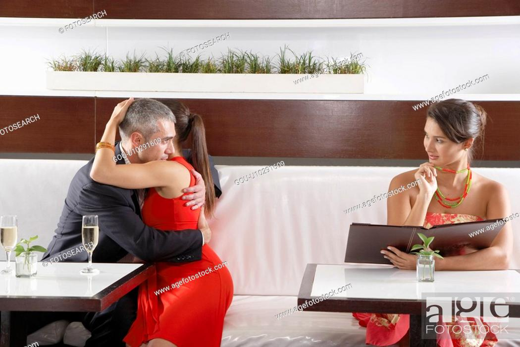 Stock Photo: Man hugging girlfriend and flirting with other woman.