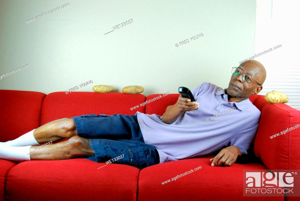 Stock Photo: A senior citizen relaxing on a couch with a remote control in hand and potatoes on the couch.