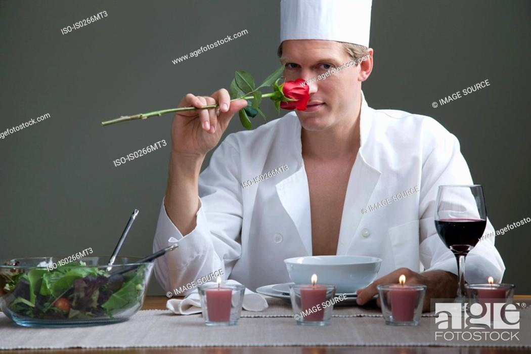 Stock Photo: A man in chefs outfit smelling a rose and a romantic meal.