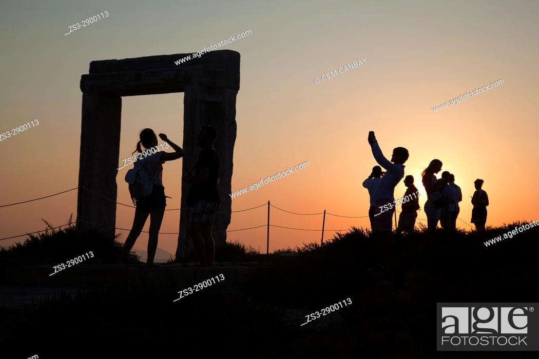 Stock Photo: Silhouettes of the tourists at the famous Portara, unfinished door of Apollon Temple, in town center at sunset, Naxos, Cyclades Islands, Greek Islands, Greece.