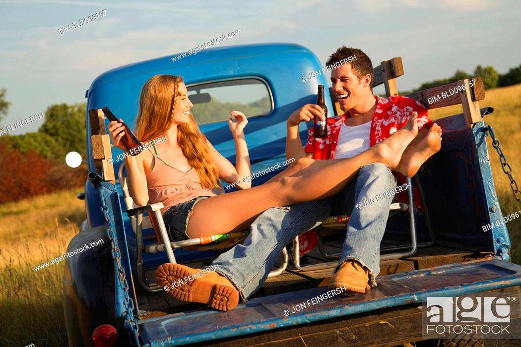 Stock Photo: Caucasian couple drinking beer in back of truck.