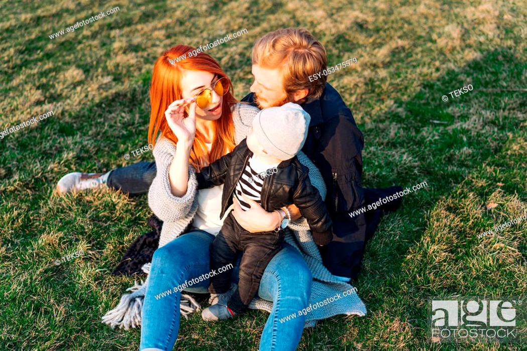 Stock Photo: happy mom dad and son hugging in the park on a sunny day.