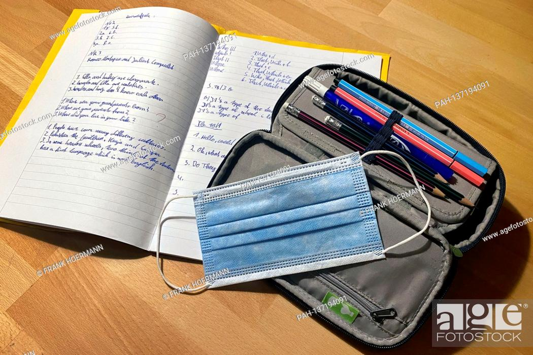 Stock Photo: Topic picture school in times of the coronavirus pandemic, students must wear a mask. Still life, pencil case, pencil case, exercise book.