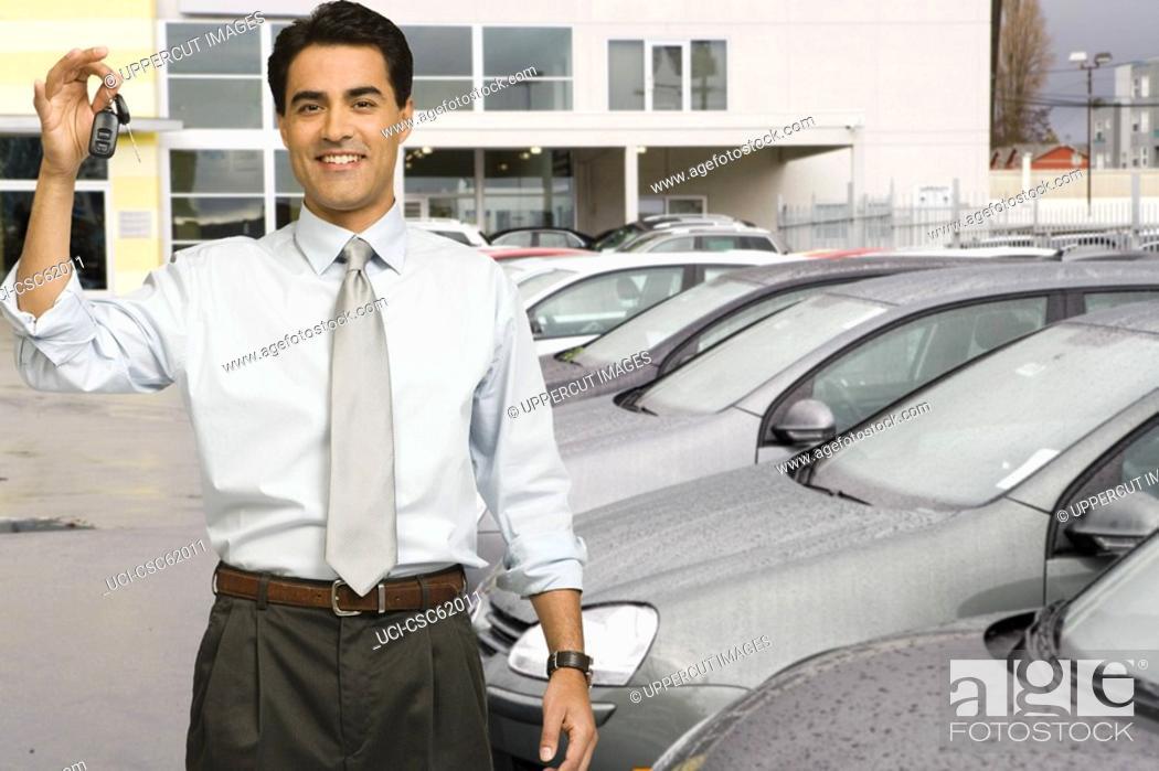 Stock Photo: Man holding car keys at car dealership.