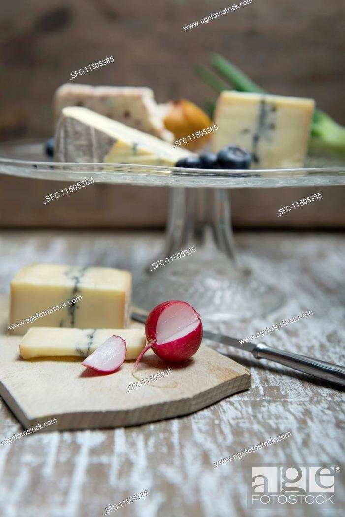 Stock Photo: Jacobean sage, Cambozola, Morbier and Wensleydale on a glass stand with radishes and Morbier on a wooden board.
