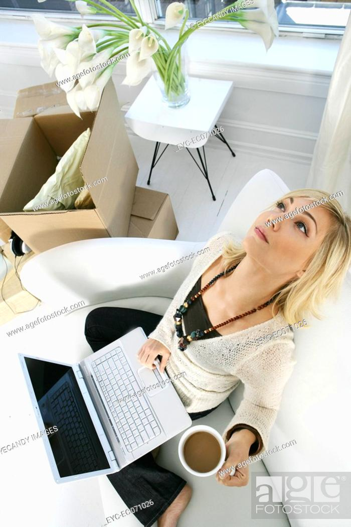 Stock Photo: Young woman using laptop at home.