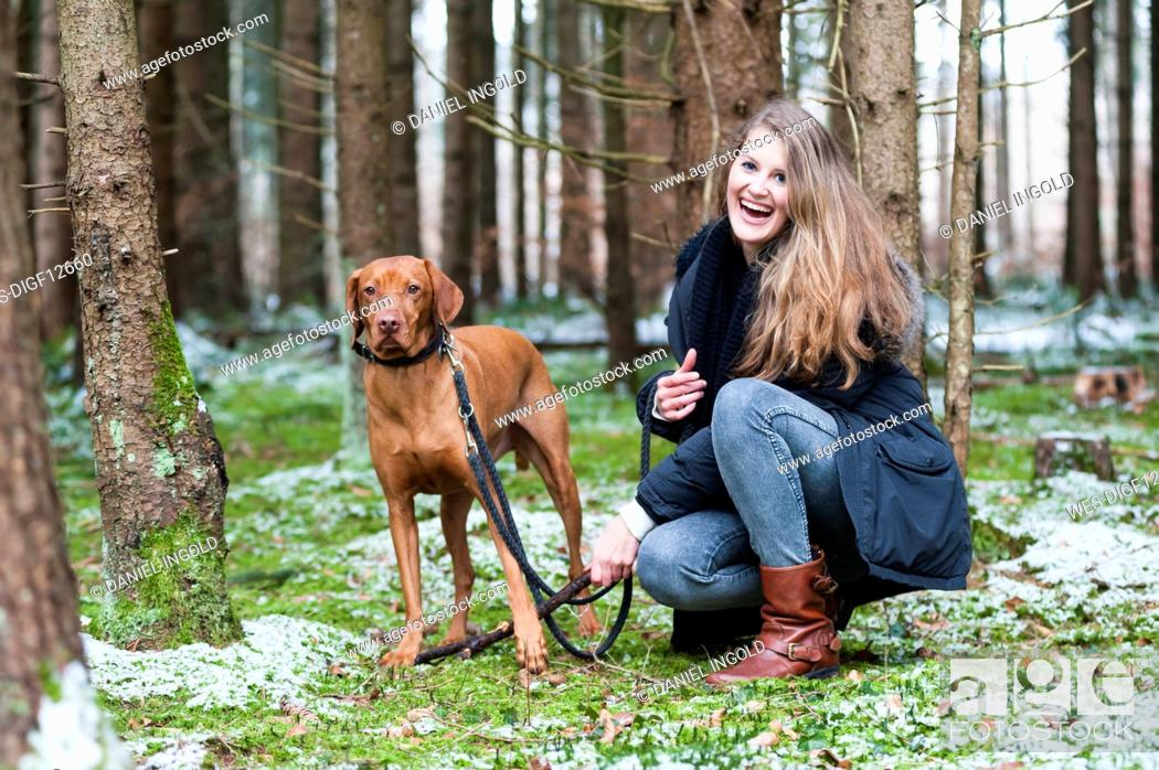 Stock Photo: Smiling young beautiful woman with long brown hair crouching by dog against trees in forest.